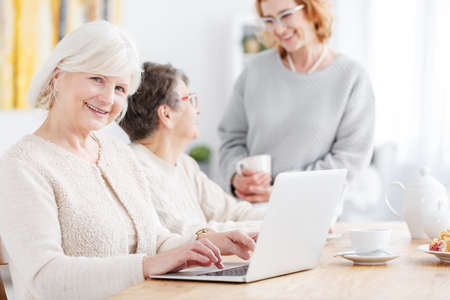 Elderly woman sitting at table with laptop doing online shopping smiling at camera while other senior ladies are talking in the background