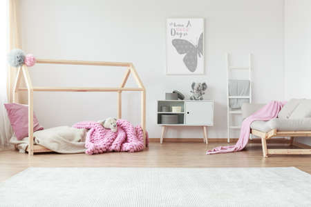 Creative kid bedroom with patterned pink blanket and pillow in scandi style