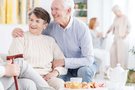 Old couple enjoying retirement together in senior care and support center in the company of friendly people
