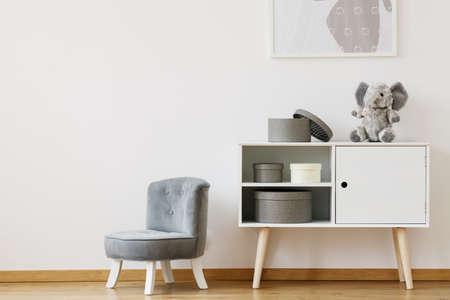 Grijze stoel naast witte plank met dozen en knuffel in monochromatische kinderkamer