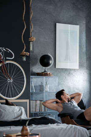 bedroom design: Man chilling on black chair in bedroom with concrete wall and black globe on metal shelf