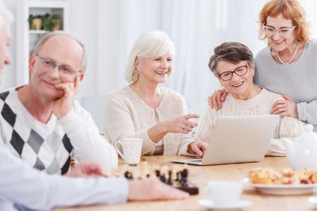 Three happy smiling senior women using laptop while elderly men are talking and playing chess sitting at communal table in a retirement home Zdjęcie Seryjne