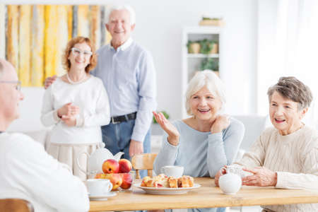 Senior friendship and happy retirement concept, group of active older people talking about the good old days enjoying tea and cake at home Stok Fotoğraf