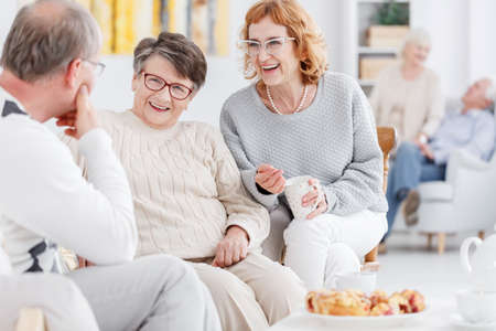 third age: Senior club concept, group of elderly people talking and enjoying each others company Stock Photo