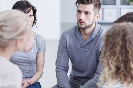 Unhappy young man sitting with other people during addiction therapy