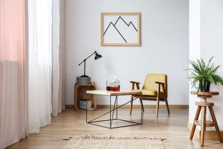 Rustic design of white apartment interior with designer armchair, modern coffee table and framed poster on the wall