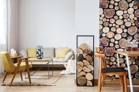Designer armchair, sofa, firewood and coffee table in warm cozy apartment with open dining area and log pile wallpaper