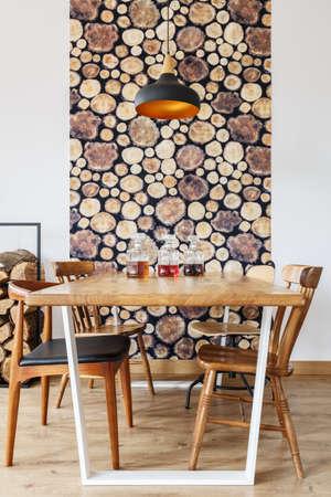 自然なデザインのモダンで明るいダイニングルームで木製のダイニングテーブル、椅子、壁の装飾 写真素材