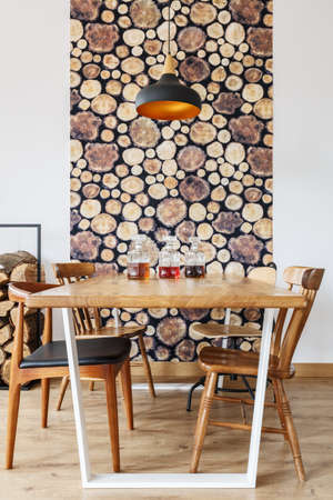 Wooden dining table, chairs and wall decoration in modern bright dining room with natural design