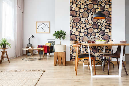 Dining table and rustic brown chairs in contemporary spacious flat with wooden accents