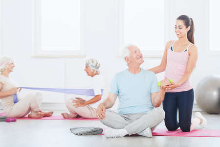 Happy elderly person sitting with crossed legs on pink mat and lifting a dumbbell with trainer supporting him