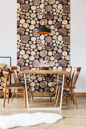 Rustic design and wooden log wall decoration in stylish modern dining room with black lamp and retro chairs