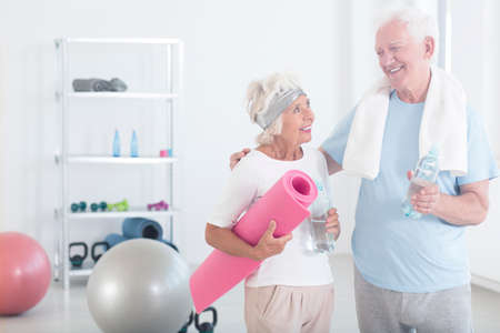 Großmutter hält rosa Fitness-Matte und lächelt Großvater vor Yoga-Kurse im Fitness-Studio