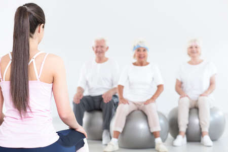 Young coach is sitting on gym ball in front of elderly people during breathing and relaxation classes