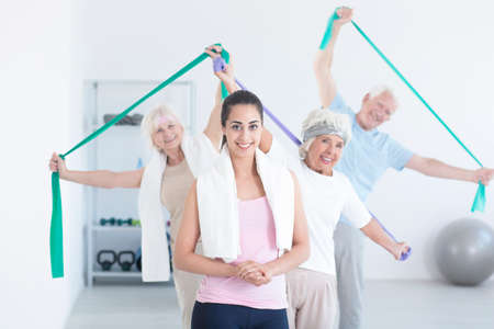 Active elderly people stretching using elastic tape while pretty young trainer standing in front of them