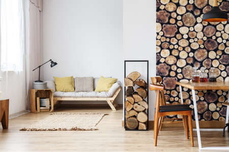 Natural design in open plan studio with log holder, wood wallpaper in separated dining room and wooden box standing next to sofa in living space