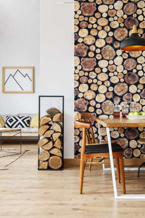 contemporary living room: Firewood holder and wooden log wallpaper in spacious interior with open living room and separated dining area