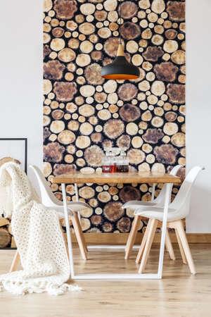 Zacht textiel en log behang in een indrukwekkende eetkamer met Scandinavische inrichting, witte stoelen en een houten gemeenschappelijke tafel Stockfoto
