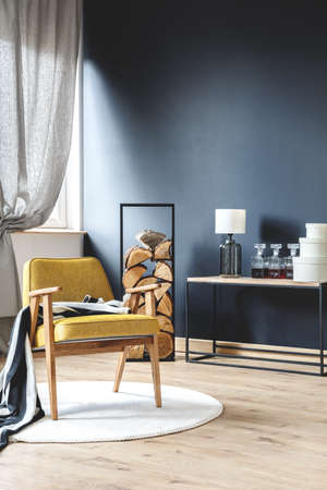 原木、黒の壁と灰色のカーテンとスタイリッシュなリビング ルームで白の敷物の上に毛布立って黄色肘掛け椅子木製