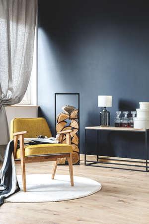 Poltrona gialla in legno con coperta sul tappeto bianco in elegante soggiorno con tronchi di legno, pareti nere e tende grigie Archivio Fotografico - 85716312
