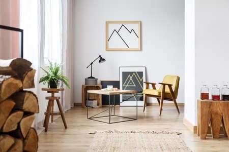 モダンなデザインのインテリアの居心地の良い白いリビングルーム、コーヒーテーブル、アームチェア、ポスター、薪