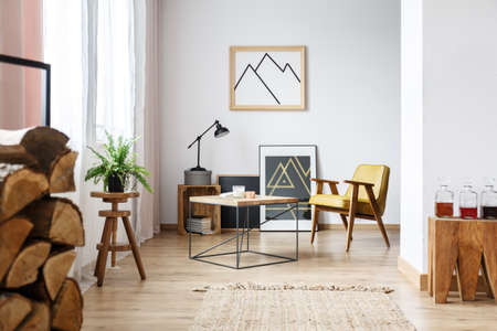 Modern ontworpen interieur van gezellige witte woonkamer met salontafel, fauteuil, posters en brandhout Stockfoto