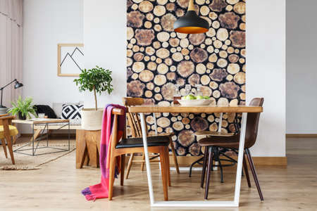 Cozy rustic design of spacious warm loft interior with wooden log wallpaper and natural tree stump