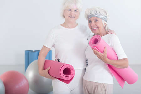 Two happy, active, elderly women holding pink mats preparing for stretching classes Stock Photo