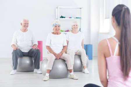 Gruppe von älteren Menschen sitzen auf Silber Turnhalle Bälle und hören junge Trainer während der Rehabilitation im Zimmer mit Ausrüstung Lizenzfreie Bilder