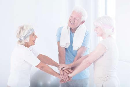Glückliche aktive ältere Freunde in Sportbekleidung unterstützen sich gegenseitig während der körperlichen Aktivität im Fitnessstudio