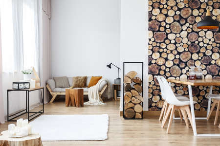 Wooden log texture wallpaper in cozy dining space of white open plan apartment with sofa, rug and tree stump accessories Lizenzfreie Bilder
