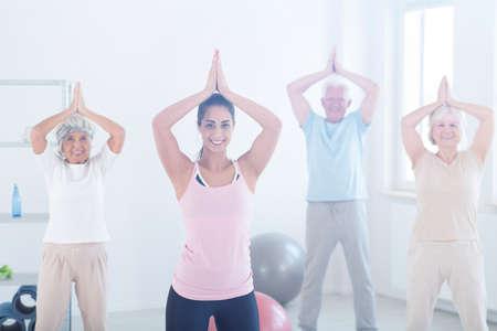 Gruppe von älteren Menschen und lächelnd Trainer eine Pose während Yoga-Kurse in Fitness-Studio Lizenzfreie Bilder