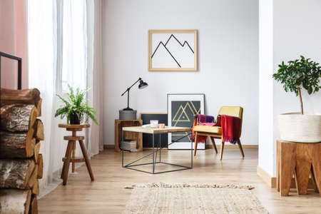 living room window: Simple wooden design in open plan, bright living room interior with armchair, minimalist poster and firewood