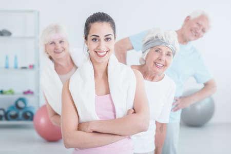 Ältere Frauen und Mann stehen hinter lächelnd Trainer mit Handtuch nach Dehnung Klassen in der Turnhalle Lizenzfreie Bilder
