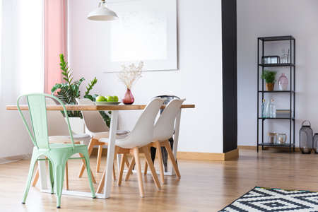 Lamp above table under window with pink curtain in pastel dining room with white and mint chairs