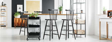Spacious open loft interior in modern vintage style with black shabby chic barstools standing at kitchen island with wooden countertop Stock Photo