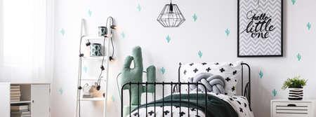 Ontwerplamp boven klein bed in kinderkamer met witte ladder leunend op wit behang met cactusmotief