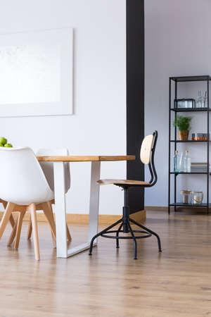 #86166908   Klassischer Holzstuhl Am Tisch Auf Bretterboden Im Geräumigen  Esszimmer Mit Malerei Auf Weißer Wand