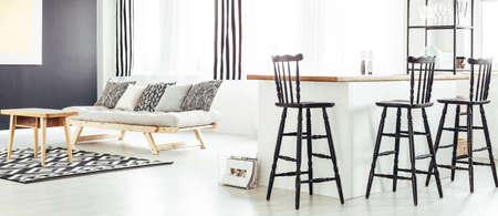 Offener Essbereich mit Retro-Barhockern in zeitgenössischem Schwarz-Weiß-Interieur mit Sofa, gemustertem Teppich und Couchtisch aus Holz Standard-Bild - 86166910