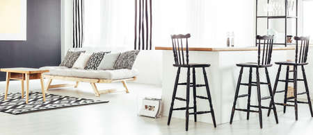 Open dining area with retro barstools in contemporary black and white interior with sofa, patterned rug and wooden coffee table