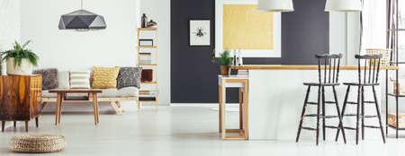 Einfaches Sofa mit gemusterten Kissen, Couchtisch und gelber Malerei auf schwarzer Wand in der hellen Wohnung des offenen Raumes mit Kücheninsel und rustikalen Barhockern Standard-Bild - 86166911