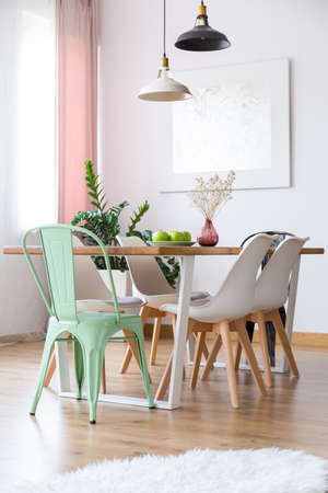 Lamps above table with vase and white and mint chairs in minimal bright dining room