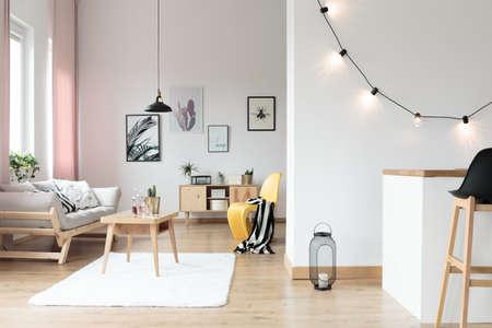 Beleuchtung im hellen Wohnzimmer mit gestreiften Decke auf gelben Stuhl neben dem Tisch auf weißen Teppich Standard-Bild - 86147707
