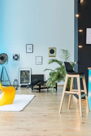 Entdeckender eklektischer Dachboden mit Barhocker, Lampe und Plakaten auf weißer Wand und Bretterboden Standard-Bild - 86147708
