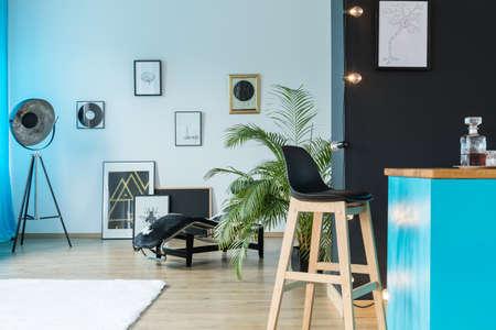 Vinyl-Schallplatten und Designer-Lampe im geräumigen Studio mit Holz-Barhocker auf Kücheninsel Standard-Bild - 86147710