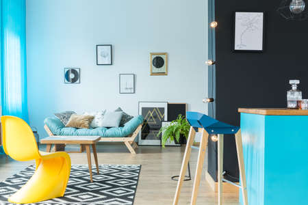 Moderner Designer-Barhocker in der blauen Kücheninsel im farbenfrohen Wohnzimmer mit gelbem Stuhl Standard-Bild - 86147729