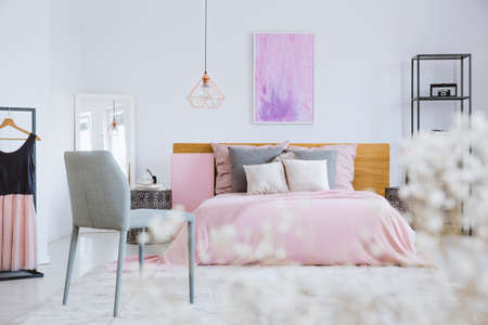 Pink, feminine bedroom with watercolor painting and simple gray chair White flowers in the foreground