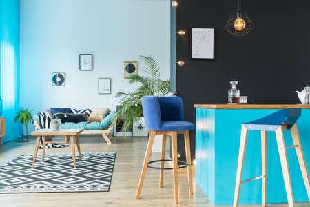 다기능 방에 검은 벽에 부엌 섬에서 파란색 스웨이드 barstool