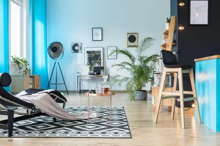 기하학적 카펫에 구리 테이블과 chaise 라운지가있는 아늑한 개방형 공간의 Barstool 스톡 콘텐츠 - 86147738