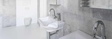 2 개의 흰색 분지, 변기 및 콘크리트 벽이있는 새로운 미니멀리스트 욕실 스톡 콘텐츠